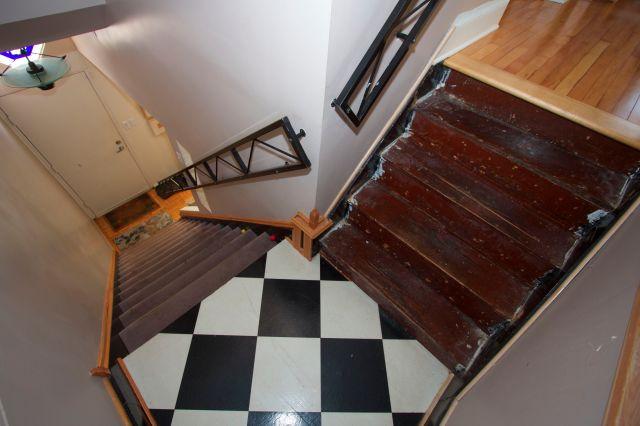 The original stairway landing of black and white vinyl tiles.